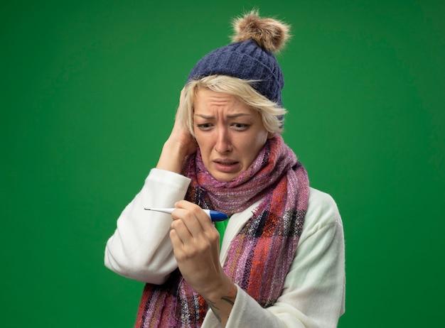 Chora niezdrowa kobieta z krótkimi włosami w ciepłym szaliku i czapce źle się czuje patrząc na termometr w dłoni, martwiąc się stojąc na zielonym tle