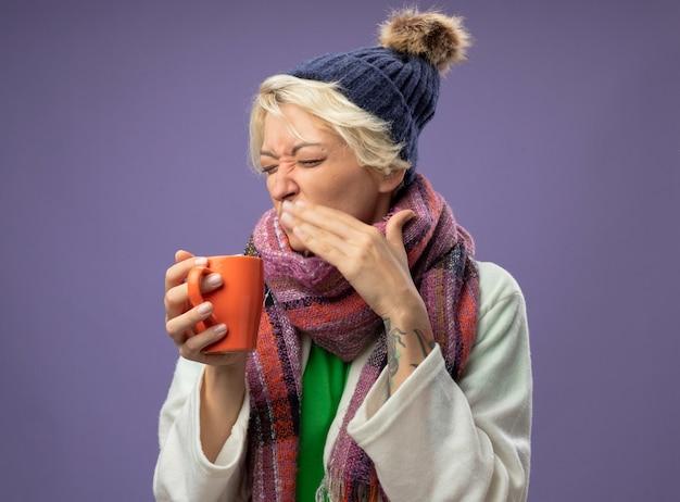 Chora niezdrowa kobieta z krótkimi włosami w ciepłym szaliku i czapce źle się czuje trzymając filiżankę gorącej herbaty idącą pić z obrzydzoną miną stojącą nad fioletową ścianą