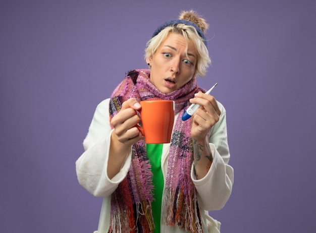 Chora niezdrowa kobieta z krótkimi włosami w ciepłym szaliku i czapce źle się czuje trzymając kubek gorącej herbaty i termometr patrząc na kubek jest zdezorientowany i zmartwiony stojąc na fioletowym tle