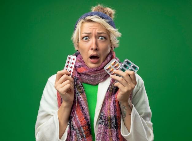 Chora niezdrowa kobieta z krótkimi włosami w ciepłym szaliku i czapce źle się czuje trzymając pęcherze z tabletkami patrząc na aparat, martwiąc się stojąc na zielonym tle