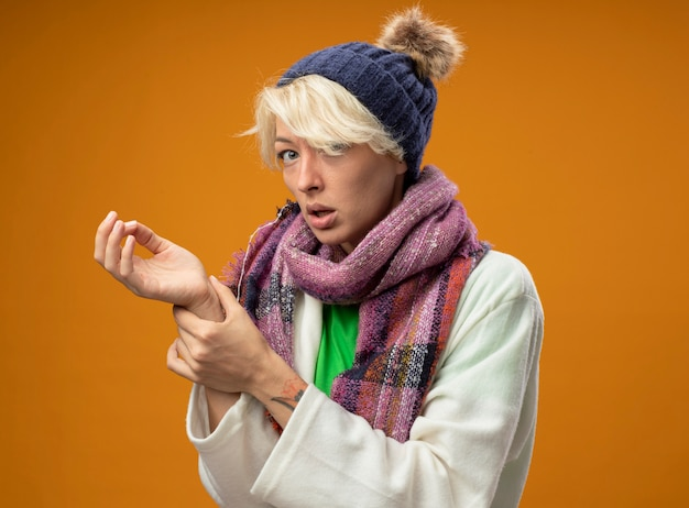 Chora niezdrowa kobieta z krótkimi włosami w ciepłym szaliku i kapeluszu, słuchająca tętna, zmartwiona, stojąca nad pomarańczową ścianą