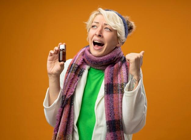 Chora niezdrowa kobieta z krótkimi włosami w ciepłym szaliku i kapeluszu trzymająca butelkę z lekarstwem zaciskająca pięść szczęśliwa i podekscytowana czuje się lepiej stojąc na pomarańczowym tle