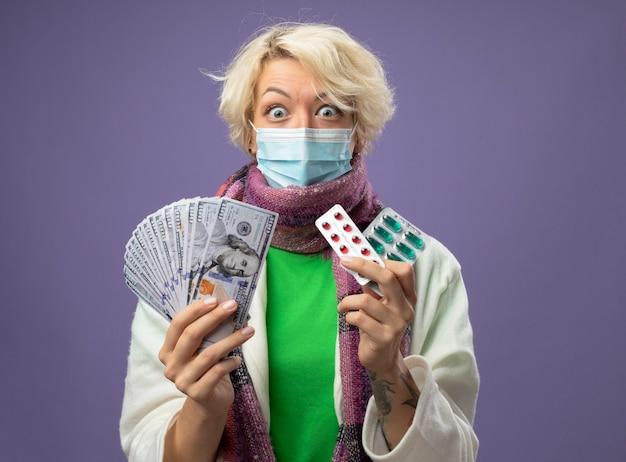 Chora niezdrowa kobieta z krótkimi włosami w ciepłym szaliku i masce ochronnej na twarz trzymająca gotówkę i blister z tabletkami patrząc na aparat, który jest w szoku stojąc na fioletowym tle