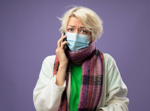 Chora niezdrowa kobieta z krótkimi włosami w ciepłym szaliku i masce ochronnej na twarz wygląda na zestresowaną i zmartwioną podczas rozmowy przez telefon komórkowy, stojąca na fioletowym tle