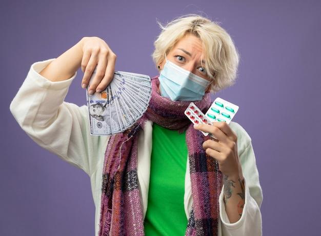 Chora niezdrowa kobieta z krótkimi włosami w ciepłym szaliku i maską ochronną na twarz trzymająca gotówkę i blister z tabletkami patrząc na kamery ze smutnym wyrazem twarzy stojącej na fioletowym tle