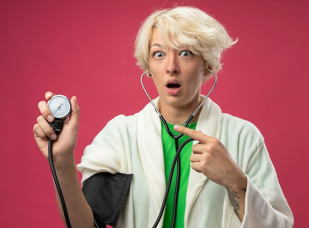 Chora niezdrowa kobieta z krótkimi włosami ze stetoskopem mierzącym jej ciśnienie krwi w panice stojącej nad różową ścianą