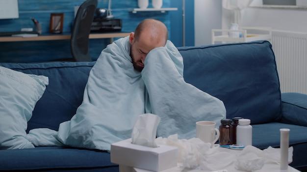 Chora osoba drżąca w kocu ma temperaturę