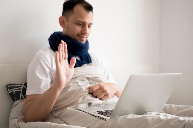 Chora osoba pozostaje w łóżku i rozmawia z przyjaciółmi