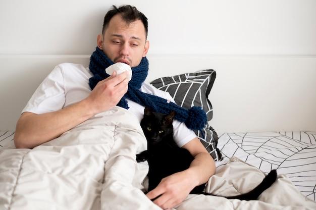Chora osoba siedzi na łóżku