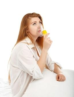Chora piękna młoda kobieta sprawia, że maska inhalacyjna do oddychania w domu izolowany na białym tle
