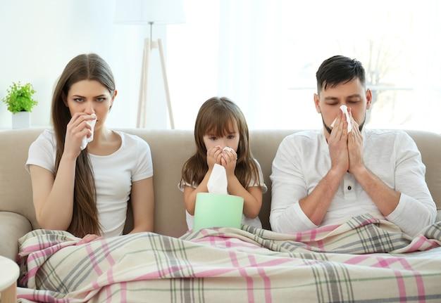 Chora rodzina siedzi na kanapie w domu