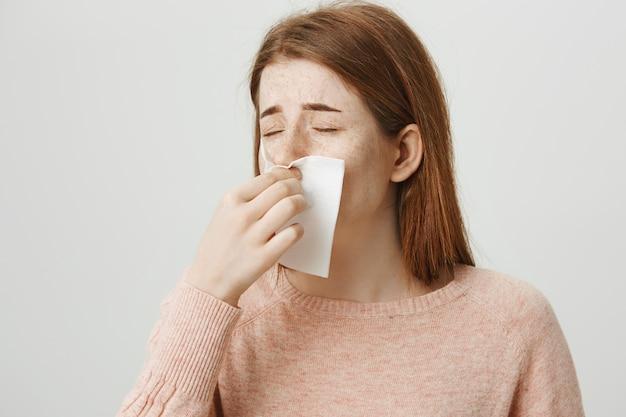 Chora ruda dziewczyna kicha w serwetkę