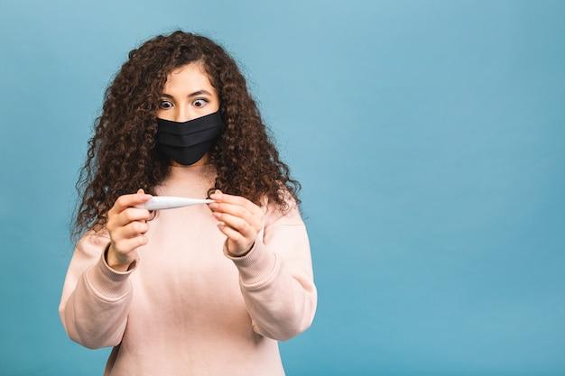 Chora smutna młoda kobieta, sterylna maska medyczna na twarz, aby zabezpieczyć się przed wirusem koronawirusa covid-19 podczas kwarantanny pandemicznej, trzymając termometr
