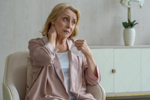 Chora starsza kobieta kicha, używając papierowej serwetki do nosa, ma katar i kaszle