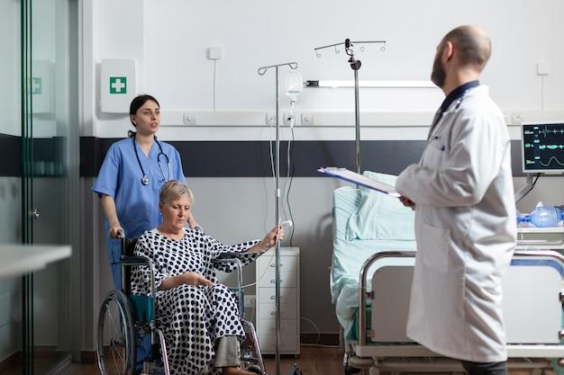 Chora starsza kobieta siedzi na wózku inwalidzkim z woreczkiem do kroplówki na ramieniu