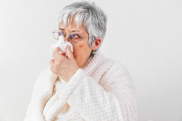 Chora starsza kobieta z papierowym wytarciem dmucha jego nos w domu.