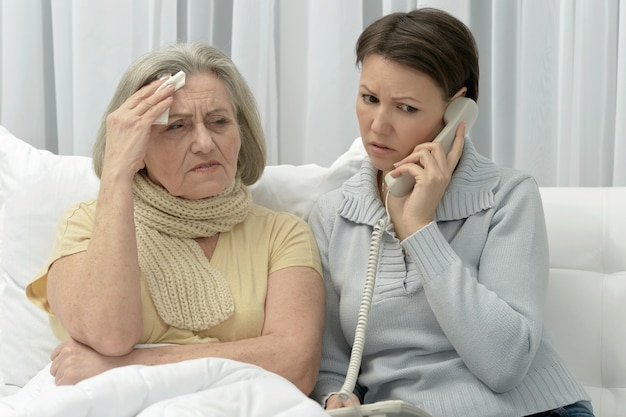 Chora starsza kobieta z troskliwą zmartwioną córką z telefonem
