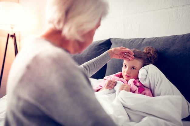 Chora wnuczka. śliczna ciemnooka wnuczka czuje się chora po zjedzeniu zbyt dużej ilości lodów