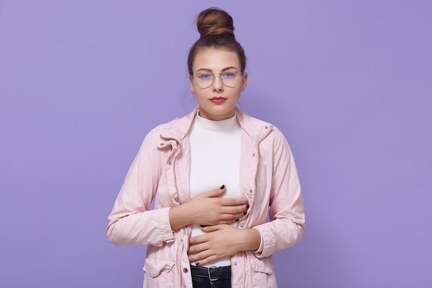 Chora, zdenerwowana dziewczyna z koką do włosów w jasnoróżowej kurtce, cierpiąca na ostry ból brzucha, zapalenie wyrostka robaczkowego, skurcz miesiączki, pozuje z rękami na brzuchu na liliowej ścianie.