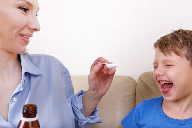 Chore dziecko i matka. mama leczy lekarstwo na syrop