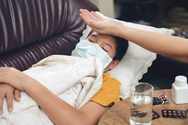 Chore dziecko leżące w rozkładanej sofie z maską ochronną na twarzy przed infekcją