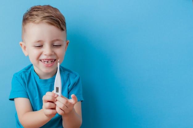 Chore małe dziecko z termometrem, mierzącym wysokość jego gorączki i patrząc w kamerę.