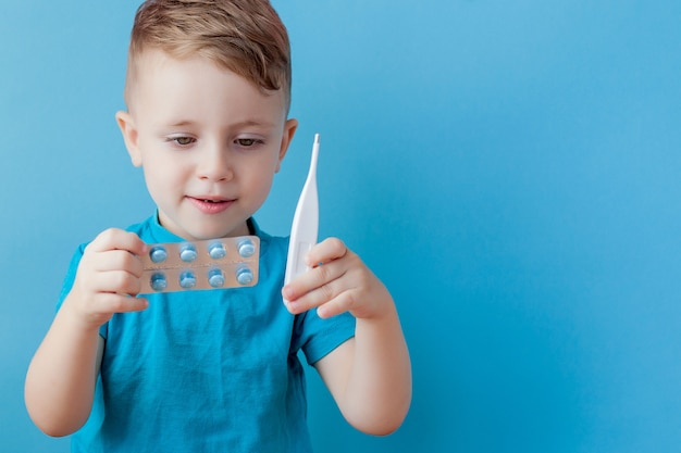 Chore małe dziecko z termometrem, mierzącym wysokość swojej gorączki i patrzącym