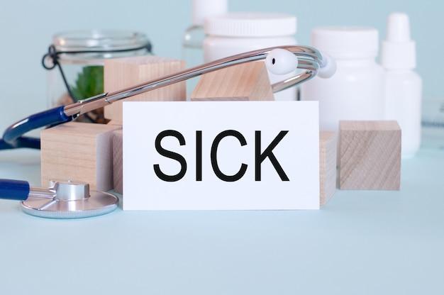 Chore słowa napisane na białej karcie medycznej, ze stetoskopem, lekarskimi pigułkami i drewnianymi klockami.