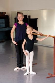 Choreograf uczy dziecko pozycji baletowych