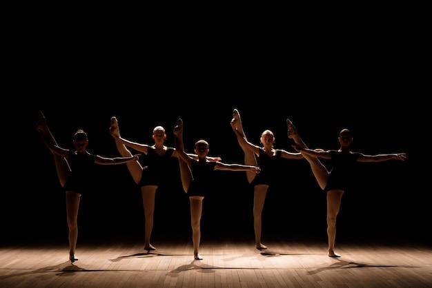 Choreograficzny taniec grupy wdzięcznych, ładnych młodych baletnic ćwiczących na scenie klasycznej szkoły baletowej.
