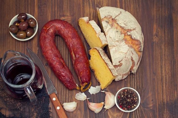 Chorizo uwędzony kiełbasiany z kukurydzanym chlebem na drewnianym tle