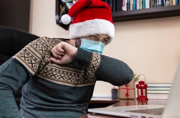 Choroba bożonarodzeniowa. młody mężczyzna w czapce świętego mikołaja i masce na twarz kaszle w łokieć i rozmawia z laptopem do rozmów wideo z przyjaciółmi i dziećmi. boże narodzenie w okresie koronawirusa.