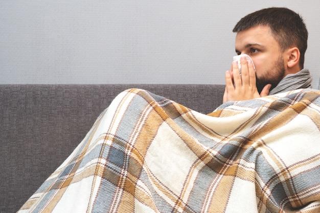 Choroba. dopinguj w domu. młody człowiek jest chory leczony w domu. dmucha jej nos w serwetkę, katar. zakażenie, epidemia, nosiciel bacillus