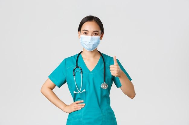 , choroba koronawirusa, koncepcja pracowników służby zdrowia. pewny siebie uśmiechnięty azjatycki lekarz, pielęgniarka lub lekarz w masce medycznej i peelingach, pokaż kciuki w górę, zapewniaj jakość, usługa guanratee
