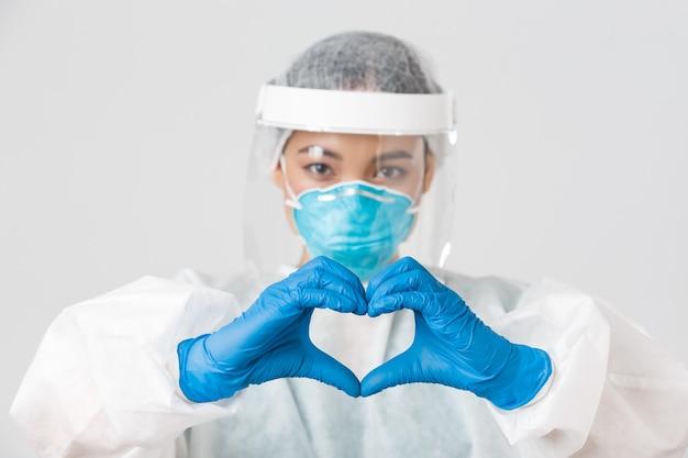 , choroba koronawirusa, koncepcja pracowników służby zdrowia. zbliżenie: pewna siebie i troskliwa azjatycka lekarka w osobistym sprzęcie ochronnym, pokazująca pacjentom gest serca
