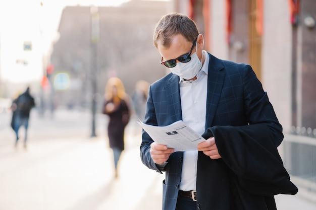 Choroba koronawirusowa. poważny bankier uważnie czyta gazetę
