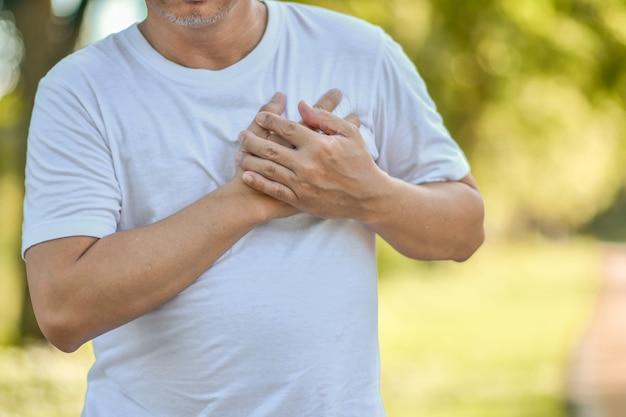 Choroba serca starszego mężczyzny trzyma rękę w sercu podczas ćwiczeń. problemy zdrowotne serca