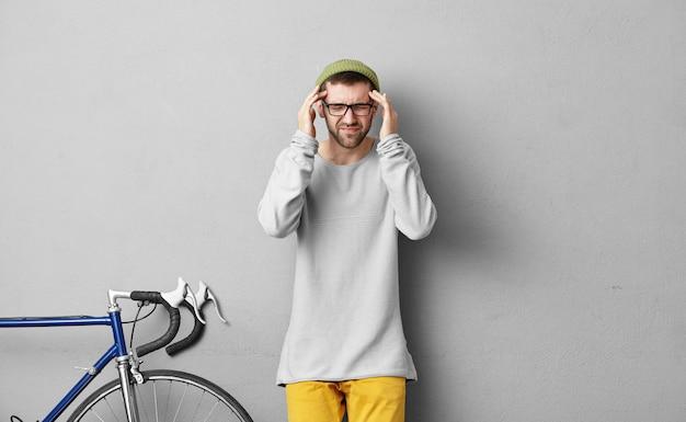 Choroby, migrena, złe samopoczucie i problemy zdrowotne. zdjęcie stylowego nieogolonego kaukaskiego faceta w żółtych spodniach, bluzie, zielonym kapeluszu i okularach ściskających skronie z powodu bólu głowy