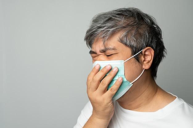 Chory azjata ubrany w medyczną maskę na twarz i kaszlący i zakrywający usta moją ręką. koncepcja ochrony przed pandemią koronawirusa i choroby układu oddechowego