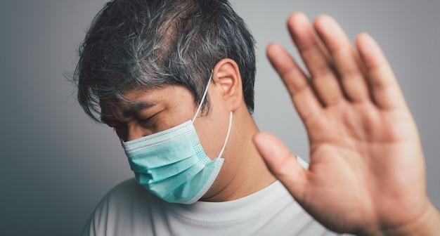 Chory azjatycki człowiek ubrany w medyczną maskę na twarz i ból barku i stres. koncepcja ochrony przed pandemią koronawirusa i choroby układu oddechowego