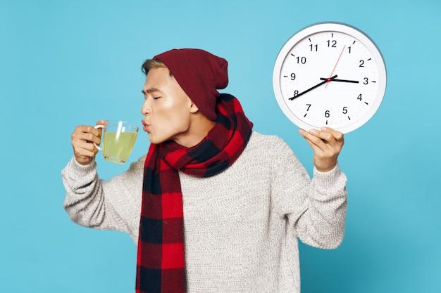 Chory azjatycki człowiek z herbatą i zegarem
