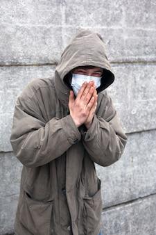 Chory bezdomny w medycznej masce przeziębił się.