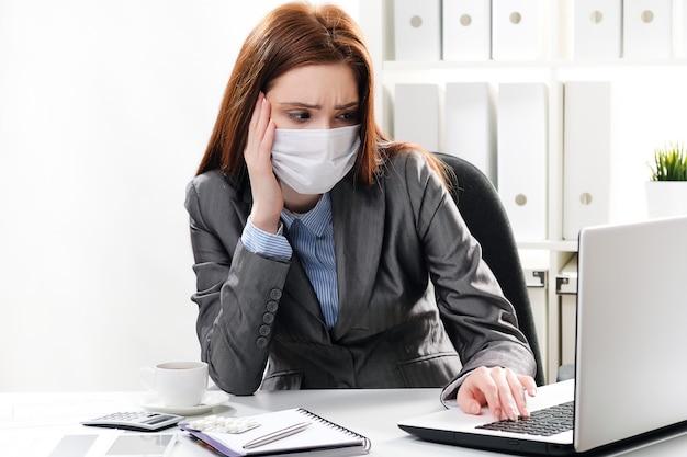 Chory bizneswoman w ochronnej medycznej masce przy biurem
