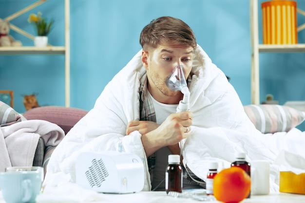 Chory brodaty mężczyzna z kominem siedzi na kanapie w domu przykryty ciepłym kocem i podczas kaszlu używa inhalatora.