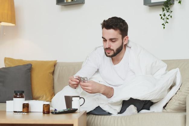 Chory brodaty mężczyzna z wysoką temperaturą ciała zażywający tabletki lub tabletki podczas pobytu w domu z powodu koronawirusa lub innej choroby