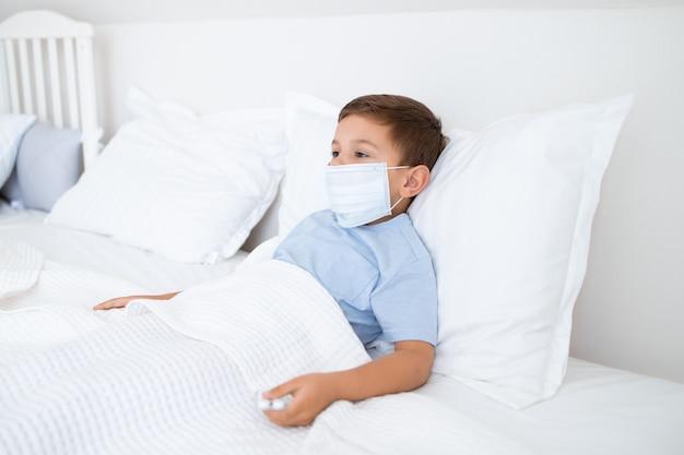 Chory chłopiec leży w łóżku w masce medycznej