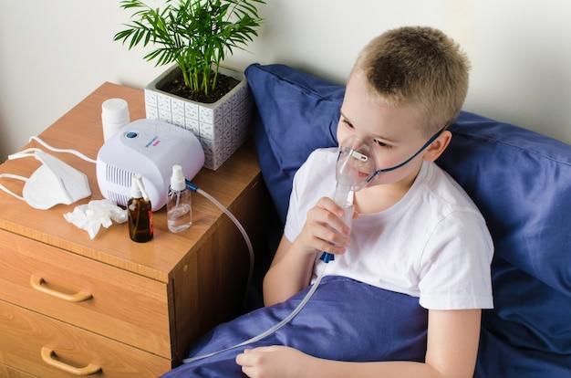 Chory chłopiec oddycha przez nebulizator