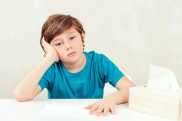 Chory chłopiec siedzi przy biurku. dziecko za pomocą papierowych serwetek. alergiczny dzieciak, sezon grypowy. chłopiec ma wirusa, katar i ból głowy.