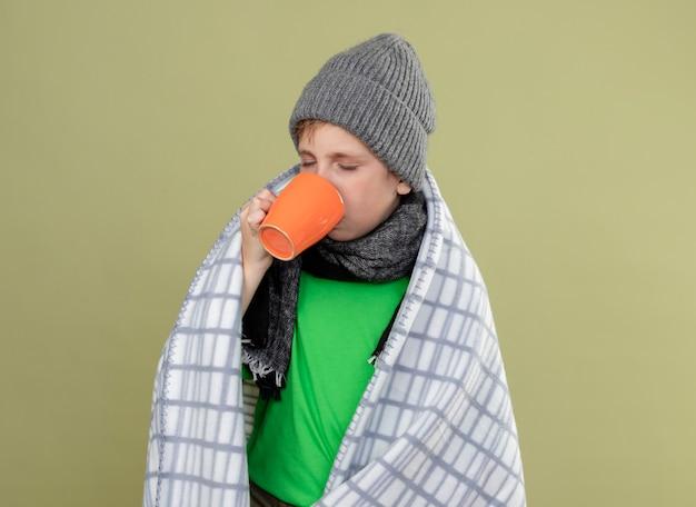 Chory chłopiec ubrany w zieloną koszulkę w ciepłym szaliku i czapce zawinięty w koc pijący gorącą herbatę stojący nad jasną ścianą