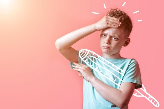 Chory chłopiec w lekkiej koszulce mierzy temperaturę termometru na kolorowym